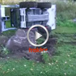 En Bobcat-förare försöker få upp den stora stenen ur gräsmattan!